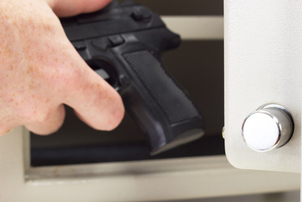Person putting firearm in gun safe